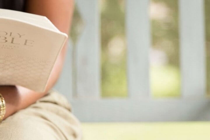 Woman on porch reading a Bible